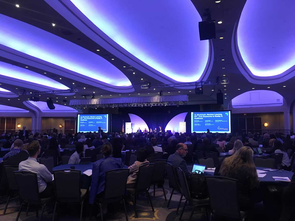 Photo of interior of the 2018 Health Datapalooza showing the stage, speakers, and a large seated audience.